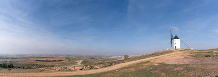 A panorama landscape with a whitewashed historic windmill typical of the La Mancha region of central Spain under a blue sky Foto de archivo