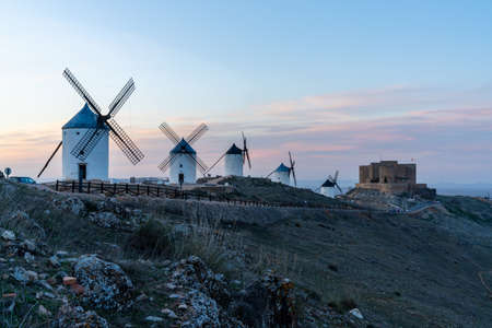 A view of the windmills and castle of Consuegra in La Mancha in central Spain at sunset
