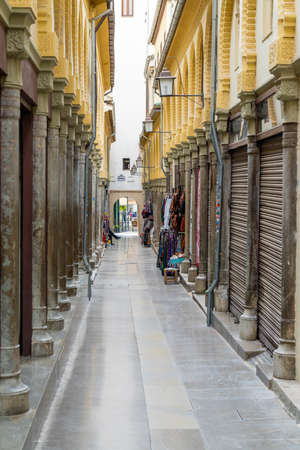 Granada, Spain - 4 February, 2021: An empty and narrow pedestrian alley in the heart of the old city center in Granada 新闻类图片