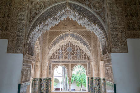 Granada, Spain - 5 February, 2021: view of detailed and ornate Moorish and Arabic decoration in the arched windows of the Nazaries Palace 新闻类图片