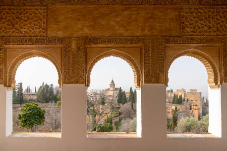Granada, Spain - 5 February, 2021: view of detailed and ornate Moorish and Arabic decoration in the arched windows of the Generalife Palace