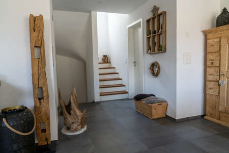 An interior view of an elegant hallway and stairs with black tile floor and white plaster walls and wooden furniture and decorative articles