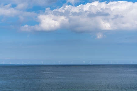 Many wind turbines in the open ocean under a blue sky with white cumulus clouds