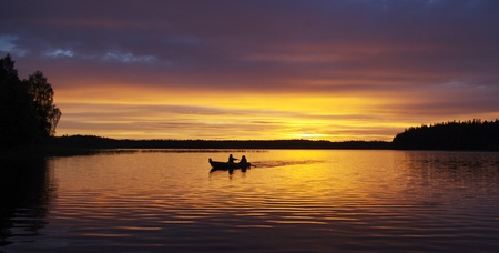 A couple in a little boat during sunset at Lake Ilgis, Plateliai, Lithuania photo
