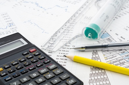 Calculator and pencil on the paper with financial graphs