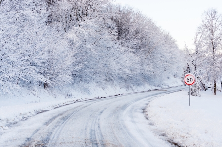 mph: Snow tracks on a country road and 60 mph km signs