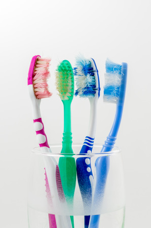 old used colorful toothbrushes in a glass