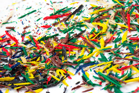 Colorful pencils shavings and debris on white background photo