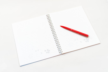 Opened new notebook and red pencil placed on the gray background photo