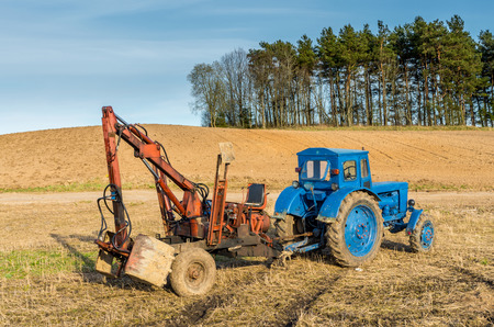 Old russian tractor with loader in Lithuanian fields photo