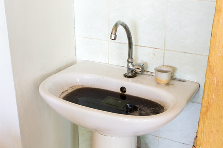 clogged: Old dirty ant clogged sink in bathroom