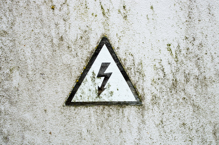 The old high voltage sign on white metal plate photo