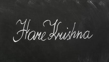 veda: The words Hare Krishna write on the blackboard. Stock Photo
