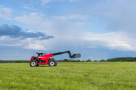 handler: Red telescopic handler in the Lithuanian fields Stock Photo