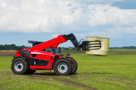 Red telescopic handler in the Lithuanian fields Stock Photo