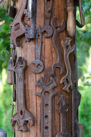 Many old wrench hung on wooden columns photo