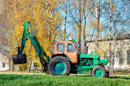 Old russian tractor with loader left at the trees