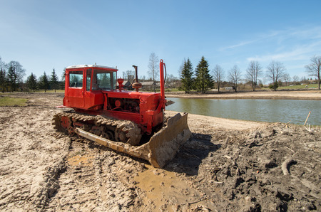 Crawler tractor with a plow on the background of rural landscape photo