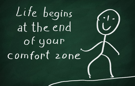 On the blackboard draw character and write Life begins at the end of your comfort zone