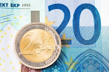 twenty euro banknote: Detail of two euro coin on blue twenty euro banknote background