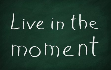 living moment: On the blackboard with chalk write Live in the moment Stock Photo