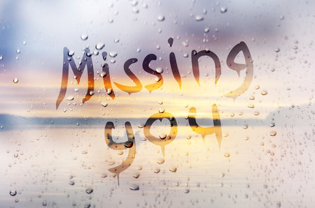 Rain on glass with Missing You text Stock Photo