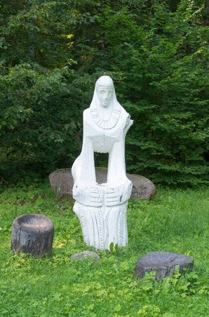 woodland sculpture: White wooden woman sculpture standing in Latvia forest