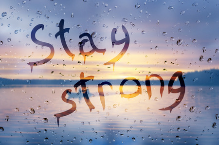 Rain on glass with Stay strong text