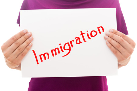 immigrate: Girl holding white paper sheet with text Immigration Stock Photo