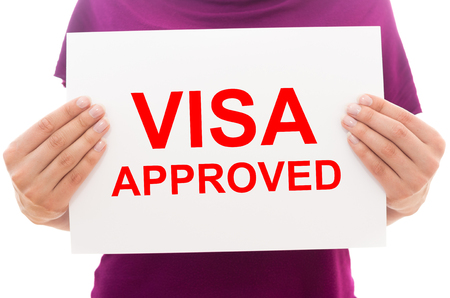 visa approved: Girl holding white paper sheet with text Visa approved