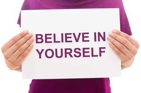Girl holding white paper sheet with text Believe in yourself