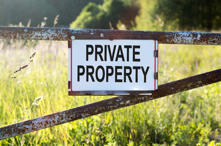 Sign Private Property on a metal gate on the dirt road