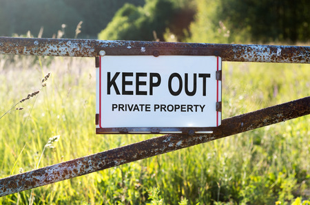 keep out: Sign Private Property and keep out on a metal gate on the dirt road