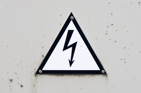 electroshock: Old and dirty high voltage sign on white metal plate