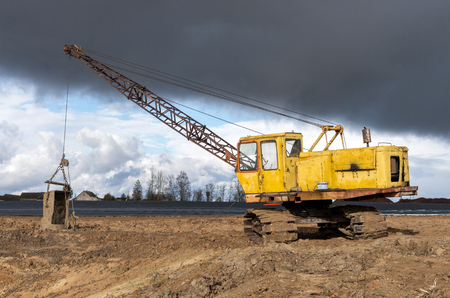 The old excavator stay in the field after works Stock Photo