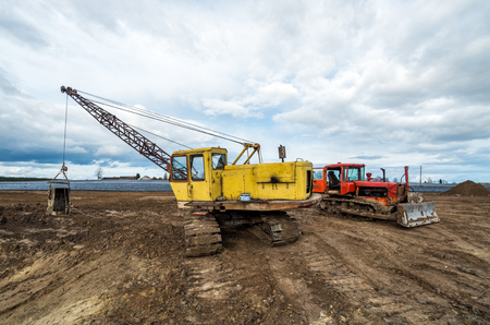 dragline: The excavator and old red tractor in the field