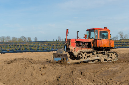 plowing: Crawler tractor with a plow on the background of rural landscape