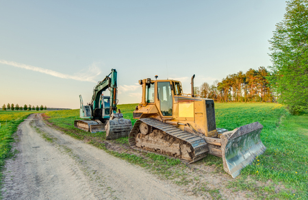 The excavator and bulldozer stayed in the field after work.