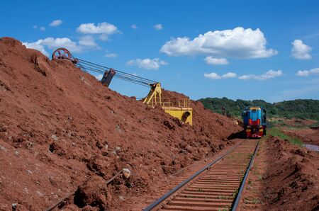 Excavator loading clay to the train on the opencast mining site Imagens