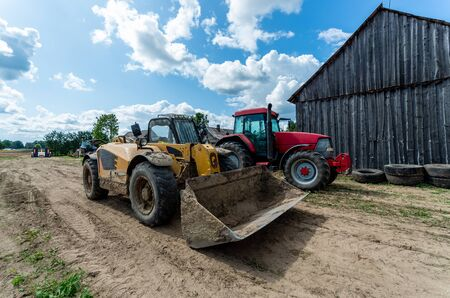 Old and dirty big loader with tractor standing by the barn