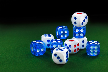 blue and white dices on the green velvet surface