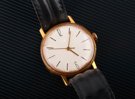 chrome man: old broken soviet wristwatch on black glossy background