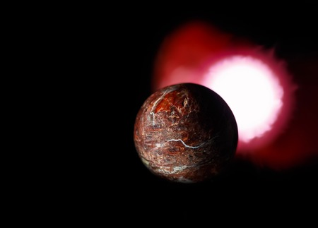 red sun: rock planet and red sun on black background. In outer space theme.