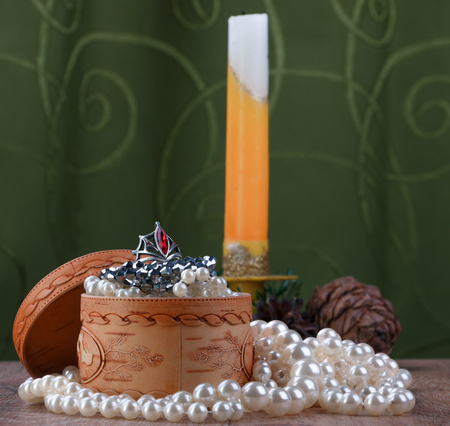 small birch bark casket with jewelry surrounded by pearls on unfocused background of candle and cones Stock Photo