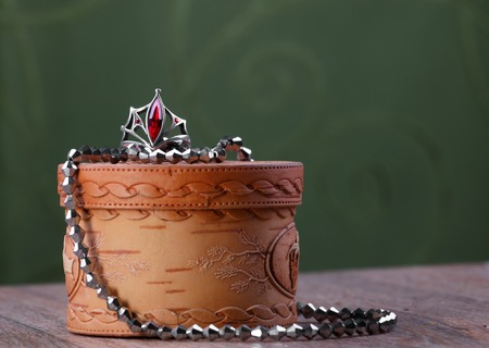 metal beads and a ring with a red stone on small closed birch bark casket on green fabric background Stock Photo