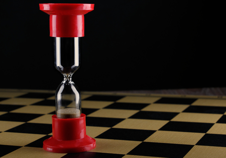 hourglass on empty chess board, shallow DOF with selective focus Stock Photo
