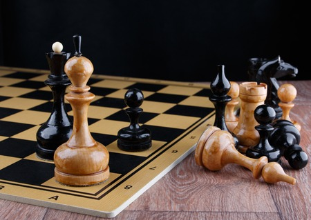 The chess pieces are placed on the chessboard. Defeated white king. Stock Photo
