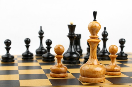 white chess king and two pawns opposite the black figures Stock Photo