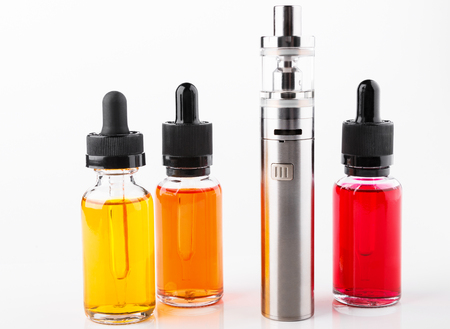 Electronic cigarette and bottles with vape liquid on white background