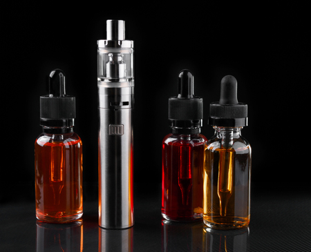 Electronic cigarette and bottles with vape liquid on black background Stock Photo